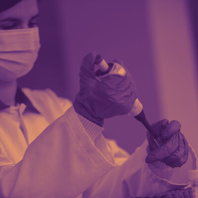 Someone Wearing Medical Attire And Purple Gloves Applying Something To A Test Tube
