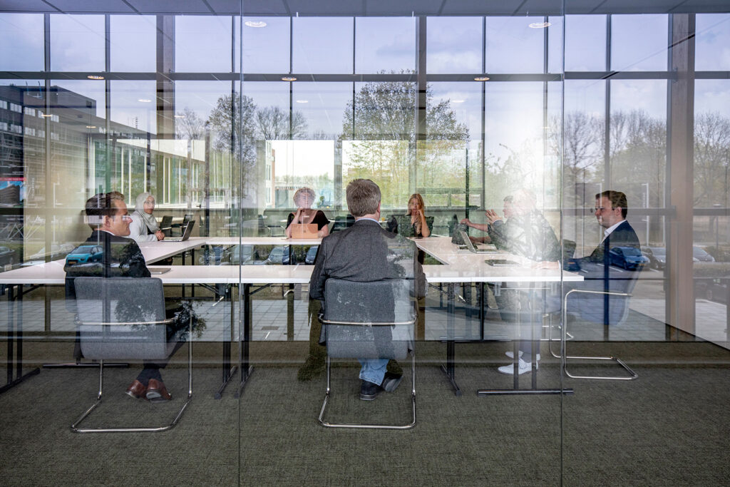 8 people in a meeting room sitting at 2 metres distance between each other